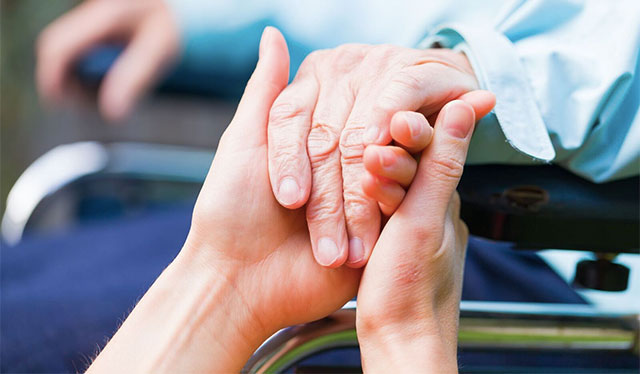 A caregiver holds the hand of an elderly patient.