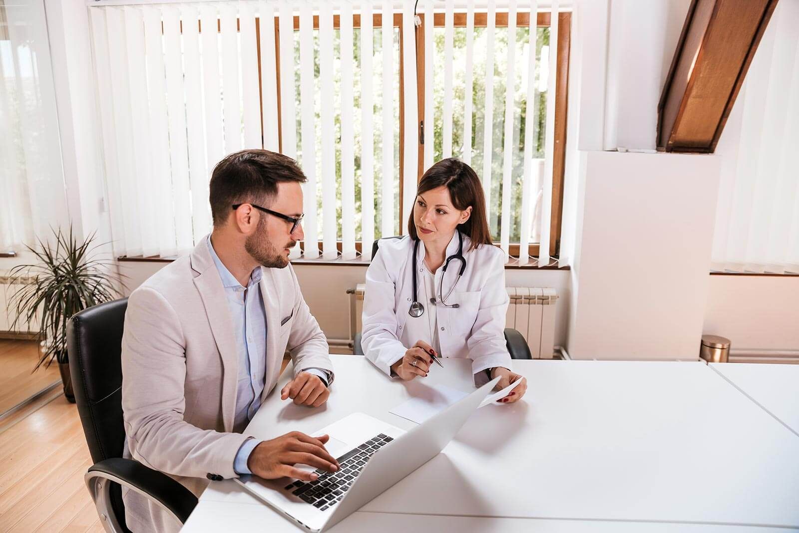 A healthcare administration manager meets with a staff doctor.