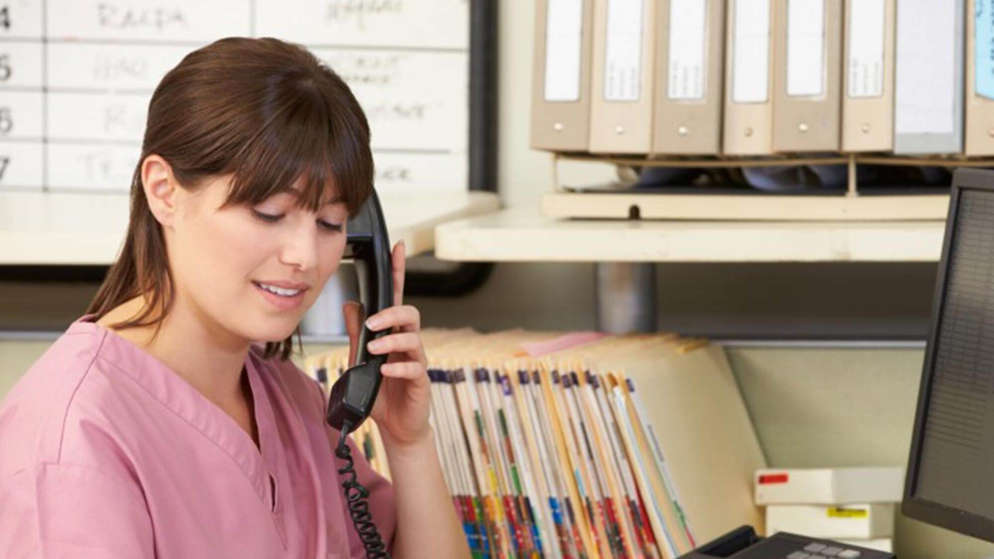 A woman in scrubs talks on the phone and reads a patient file.
