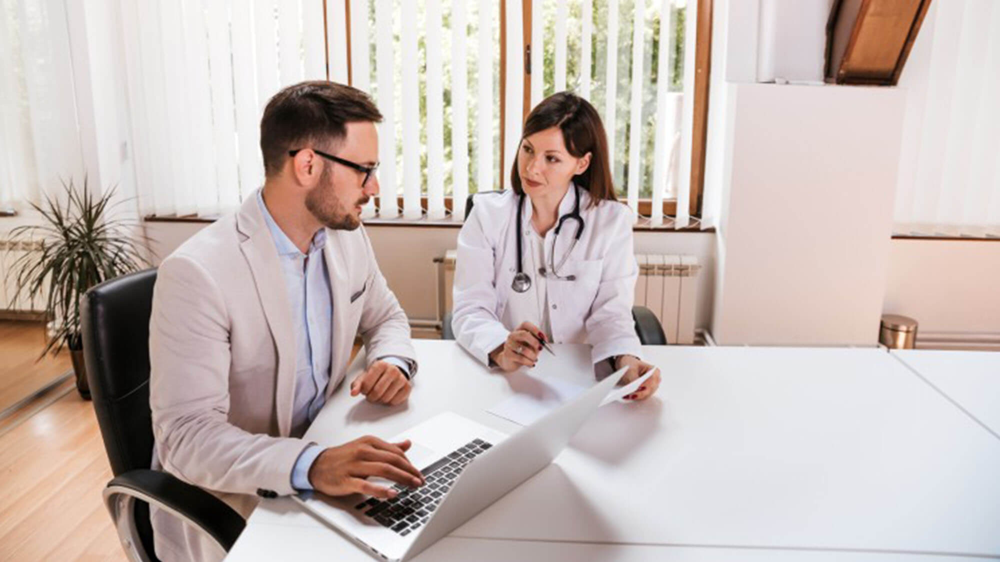Healthcare marketing manager discusses strategy with doctor.