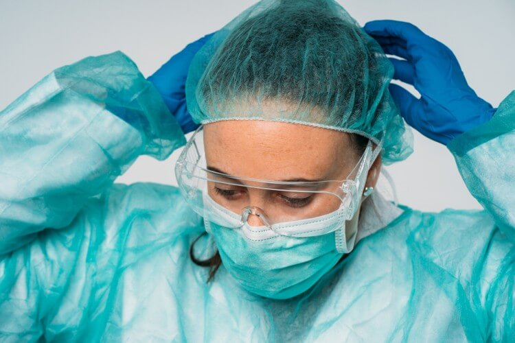 A woman with a serious expression puts on personal protective equipment, including mask, glasses, and gloves.