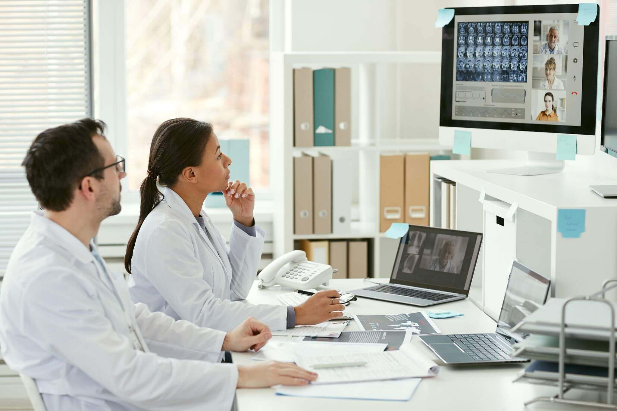 Two radiologists sit at a desk looking at MRI scans on a computer.