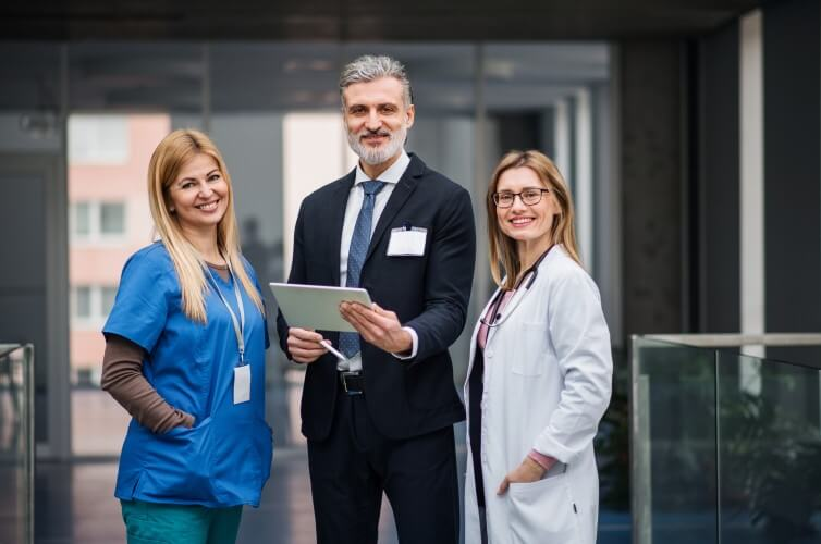 A healthcare administrator, doctor, and nurse stand together in front of a doorway.