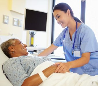 A nurse holds the hand of an older patient.