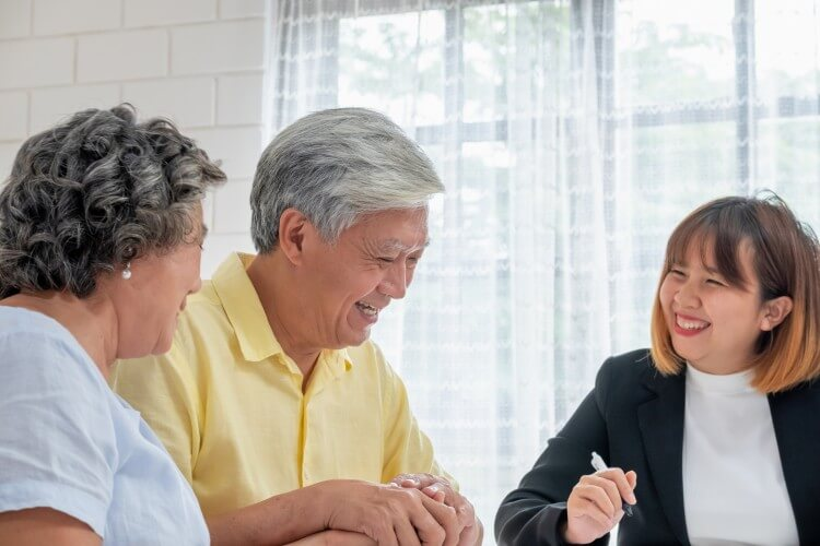 A nursing home administrator meets with an older couple.