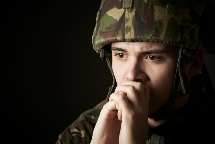 A person in a military uniform prays with their hands clasped.