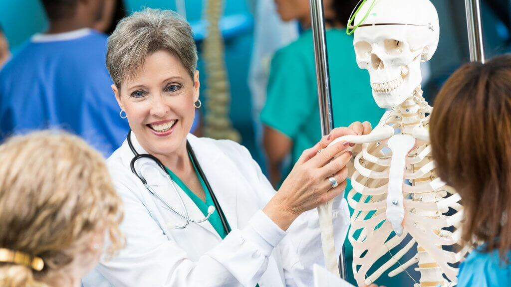 A nurse using a model skeleton to teach two students