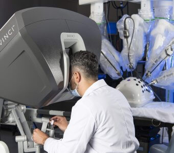 A surgeon with his face inside of a robotics display, and his hands are on the controls.